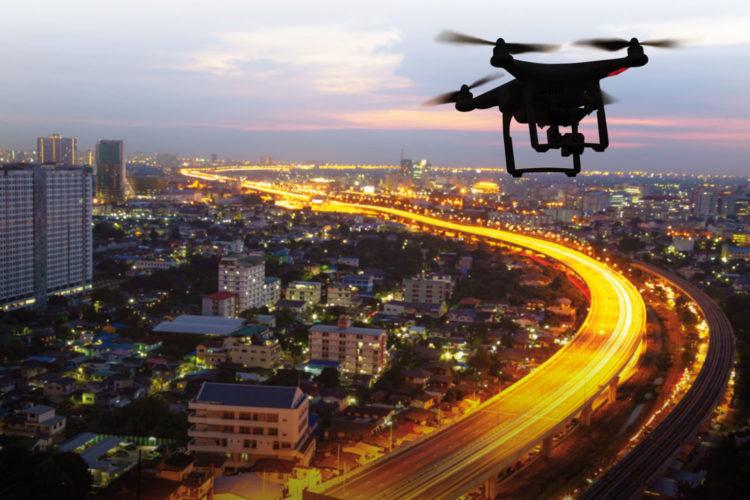 Silueta de drones sobrevolando una ciudad al anochecer.