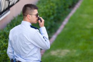 Vigilante de seguridad hablando por el walkie talkie