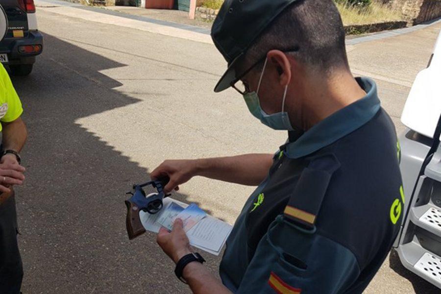 Un guardia civil inspecciona el arma de un vigilante de seguridad.