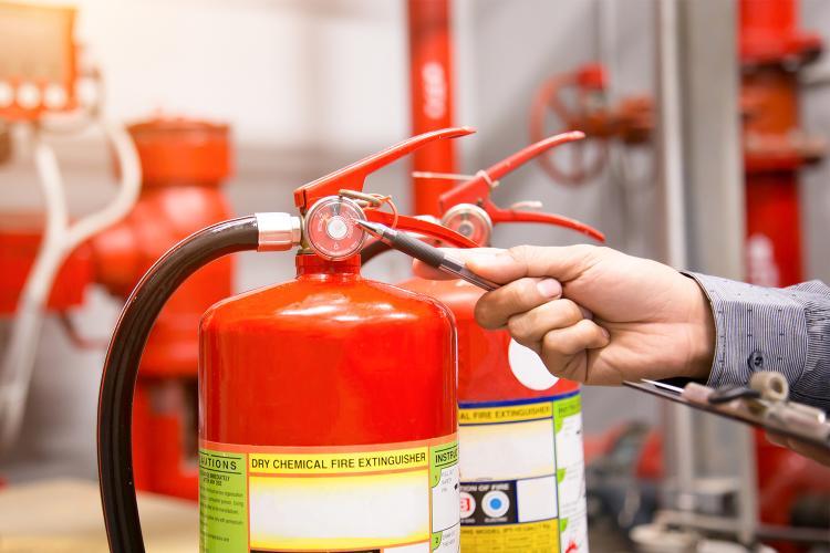 Un hombre revisa el estado de los extintores.