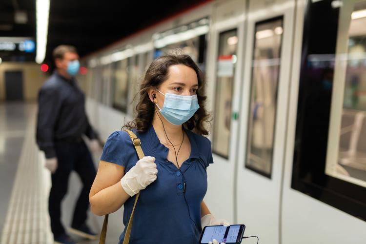 Una chica con mascarilla sube al metro.